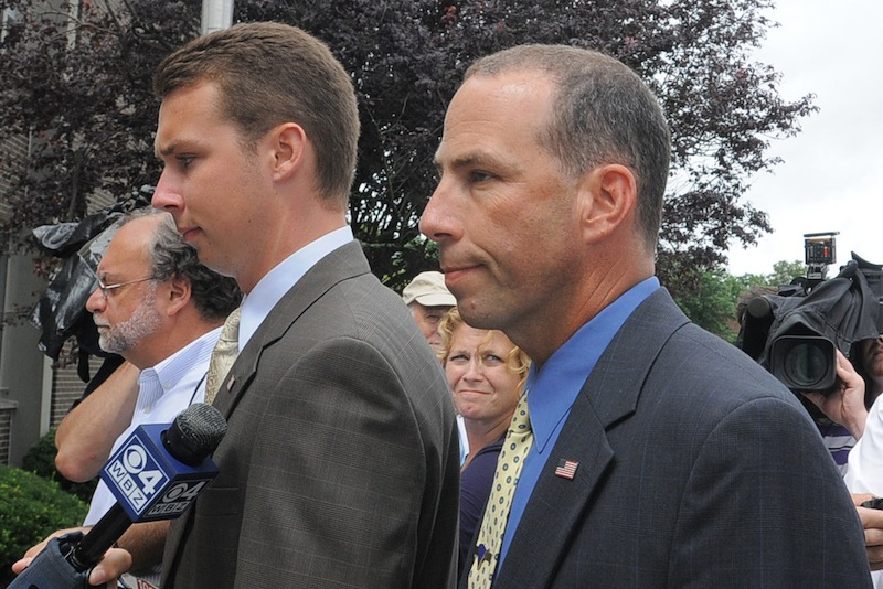 Massachusetts State Police Sgt. Sean Murphy, right, a tactical photographer, and his son Connor Patrick Murphy, arrive at State Police Headquarters for his hearing to determine his duty status after he released images of the arrest of the Boston Marathon bombing suspect, in Framingham, Mass., Tuesday July 23, 2013. Following a status hearing at state police headquarters, Murphy was placed on desk duty, where he won't have contact with the public, until a further investigation is completed, according to state police spokesman David Procopio. (AP Photo/The Boston Herald, Ted Fitzgerald) BOSTON OUT