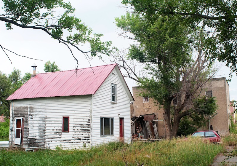 In this Aug. 26, 2013, photo is Paul Cobb's house on Main Street in Leith, N.D., where he spends his days posting online comments advocating for white supremacists to join his settlement. Cobb, 61, a self-described white supremacist, has purchased about a dozen lots in Leith and over the past year he has invited fellow white supremacists to move there and help him to transform the town of 16 people into a white enclave. No one has come, but the community is mobilizing to fight out of fear that Cobb could succeed, and the mayor has vowed to do whatever it takes to ensure Cobb's dream remains just that. (AP Photo/Kevin Cederstrom)