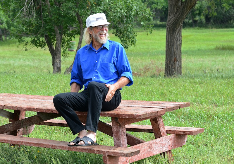 In this Aug. 26, 2013, photo Craig Cobb sits on a picnic bench in and undeveloped park in Leith, N.D., where he would someday like to hold a white power music festival. Cobb, 61, a self-described white supremacist, has purchased about a dozen lots in Leith and over the past year he has invited fellow white supremacists to move there and help him to transform the town of 16 people into a white enclave. No one has come, but the community is mobilizing to fight out of fear that Cobb could succeed, and the mayor has vowed to do whatever it takes to ensure Cobb's dream remains just that. (AP Photo/Kevin Cederstrom)