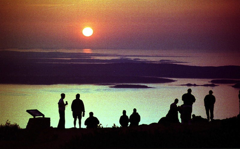 """In this September 1999 file photo, visitors to Acadia National Park watch the sunrise from the summit of Cadillac Mountain near Bar Harbor, Maine, one of the first places on the East Coast to see the sun appear. Mount Desert Island, which is linked to mainland Maine by a two-lane bridge, is ranked 25th in Travel & Leisure magazine's article, """"World's Best Islands."""" (AP Photo/Robert F. Bukaty)"""