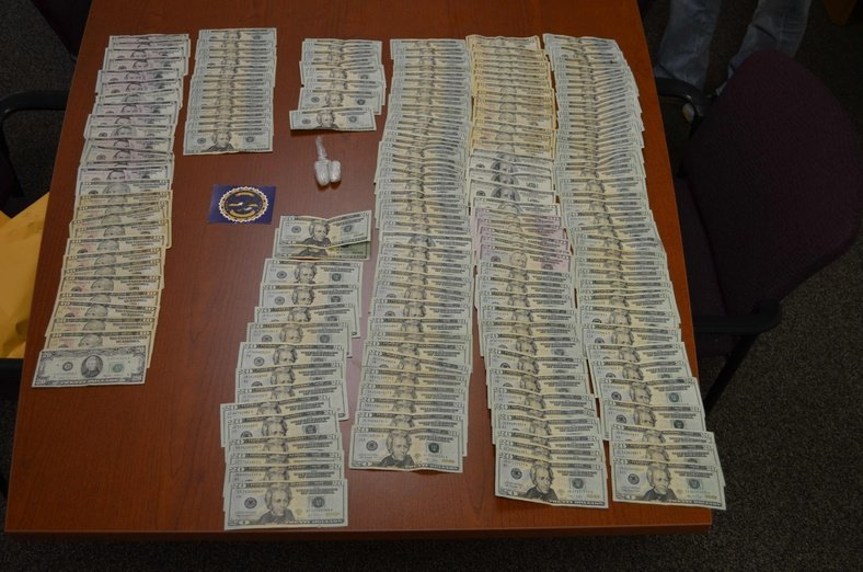 Police display cash and items found after a car chase.