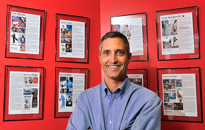 "Peter Carlisle stands in front of a gallery of his clients in his office at the MHG Ice Centre in Saco. He said when he started his own agency in 1997, he considered the growing popularity of action sports, such as snowboarding, and saw opportunity. ""He was a visionary,"" says his brother, Jeff Carlisle."