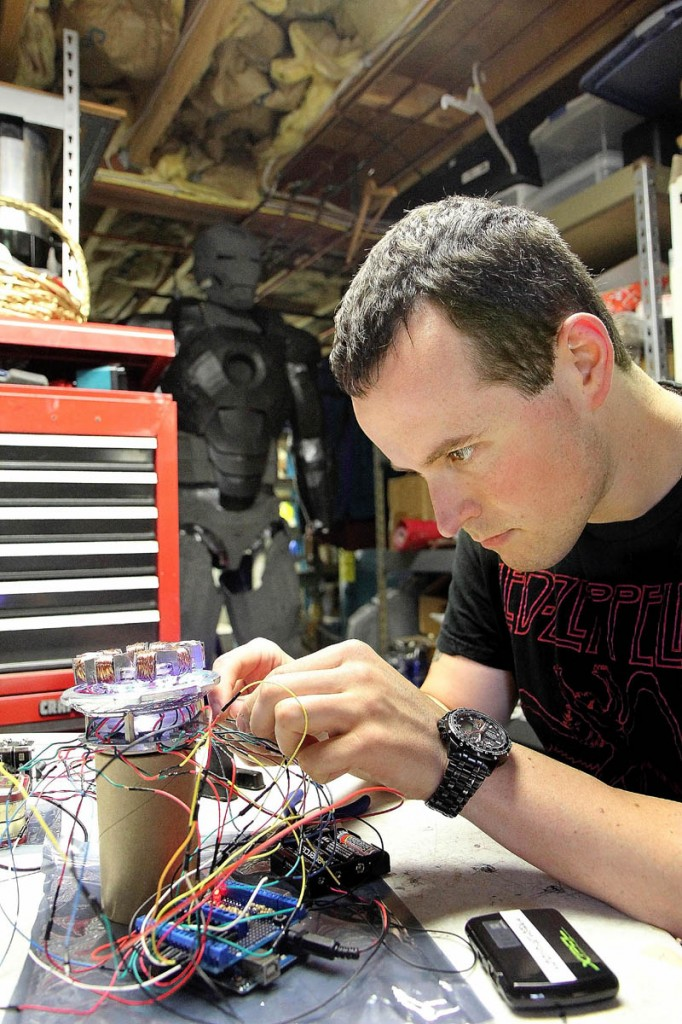 Thomas Lemieux works on an arc reactor to go on his life-size Iron Man costume, in the basement of his Oakland home recently. Lemieux, 28, said he plans to wear the costume at the Hawthorne Hotel's Halloween Ball on Oct. 26 in Salem, Mass.