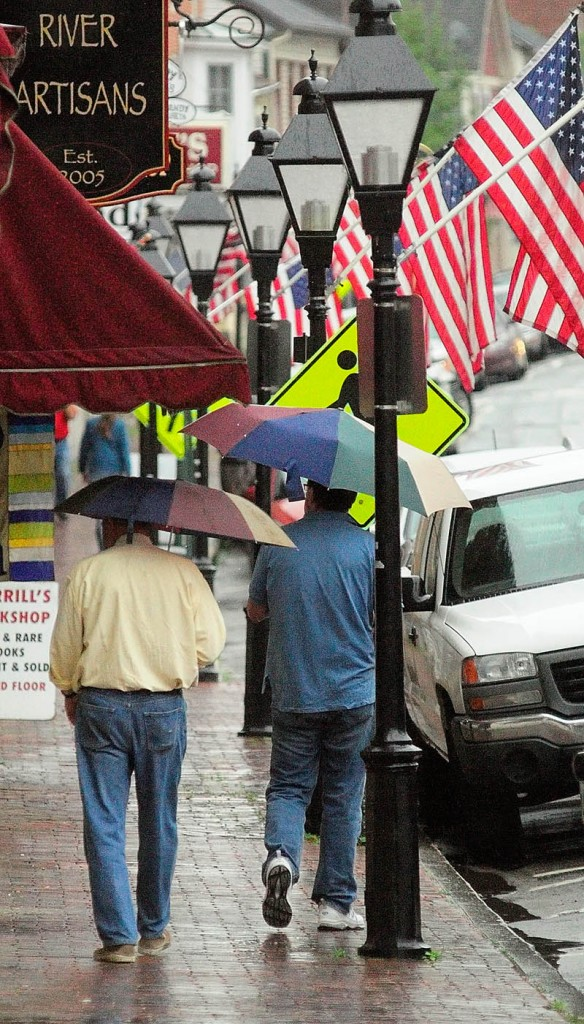 People with umbrellas walk down Water Street in Hallowell today.