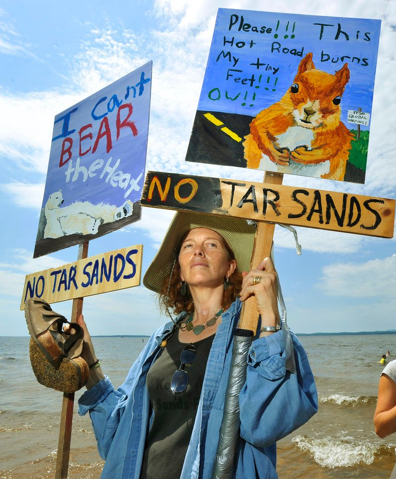 A protester holds anti-tar sands posters at a Sebago Lake State Park rally in July. Leaders at the highest levels should say
