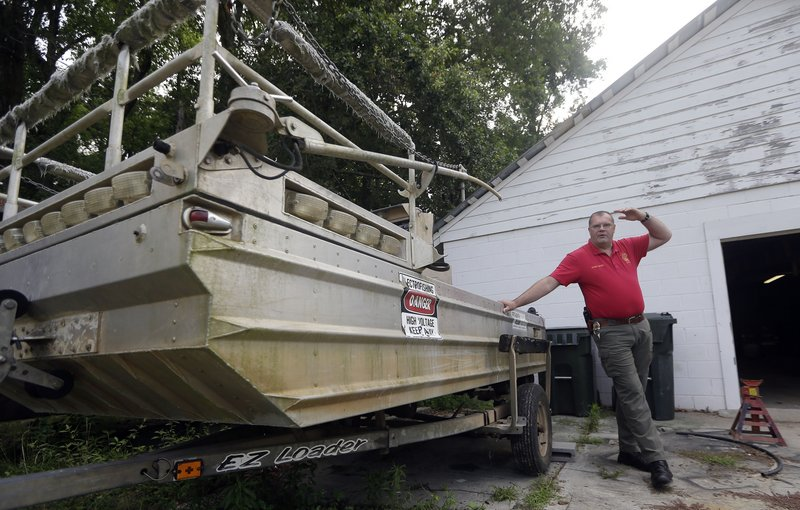 Morven Police Chief Lynwood Yates has acquired $4 million worth of military surplus over the past decade for his sleepy Georgia town of 700. Yates is standing next to one of three boats he bought.