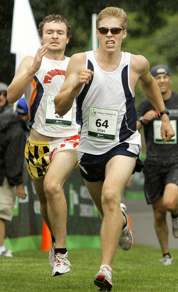 Fryeburg Academy graduate Silas Eastman, right, and Nate Hathaway of Scarborough run through the rain toward the finish line in Fort Williams.