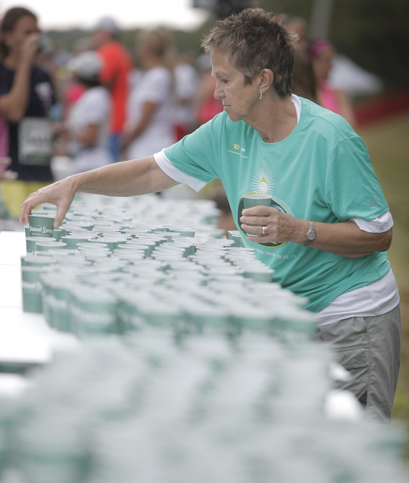 Volunteer Sue Howe of Scarborough places cups of water on a table in the staging area behind the starting line.
