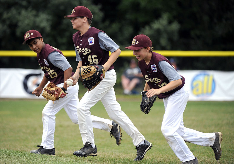 Ball caught, inning over and the Saco Little League players head to the dugout Saturday during the 12-1 victory against Newton, Mass., at the New England Little League Regionals at Bristol, Conn. From left to right are Anthony Bracamonte, Derek Madore and Andrew DeGeorge.