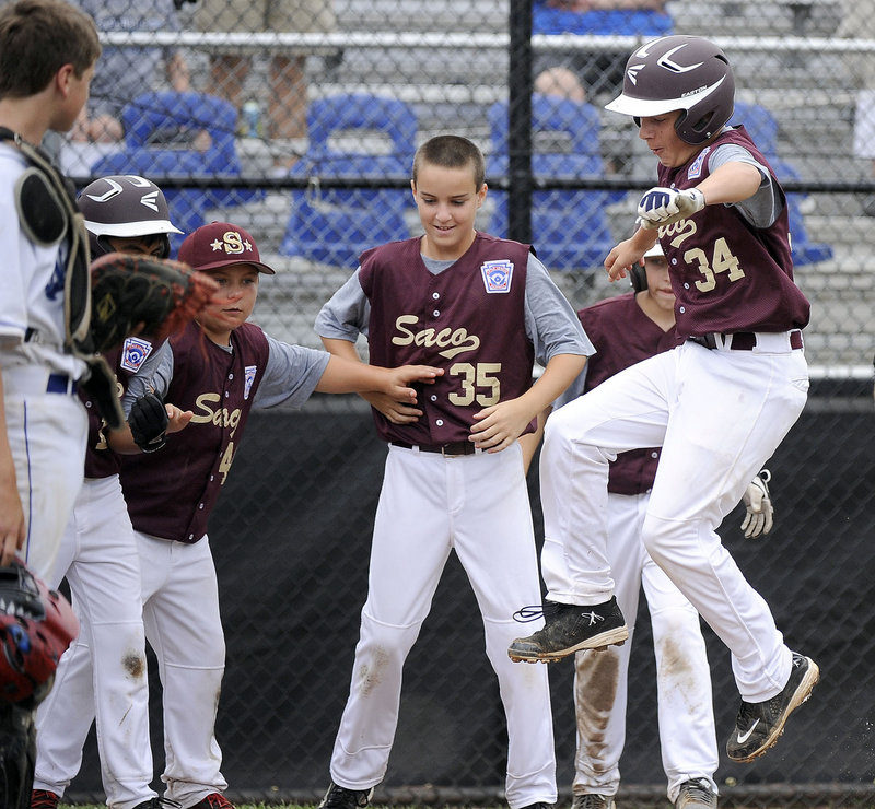 Brogan Searle-Belanger leaps on the plate Saturday after hitting a three-run homer in the third inning, giving Saco a 6-1 lead on the way to a 12-1 victory against Newton, Mass., at the Little League New England Regionals at Bristol, Conn. Searle-Belanger went 3 for 3, driving in four runs.