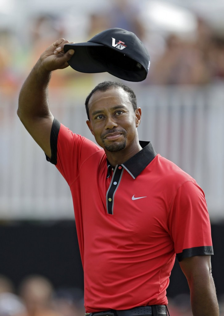 Tiger Woods waves on the 18th green of the Firestone Country Club in Akron, Ohio, after easily winning the Bridgestone Invitational on Sunday. Woods shot an even-par 70, beating defending champion Keegan Bradley and Henrik Stenson by seven shots.