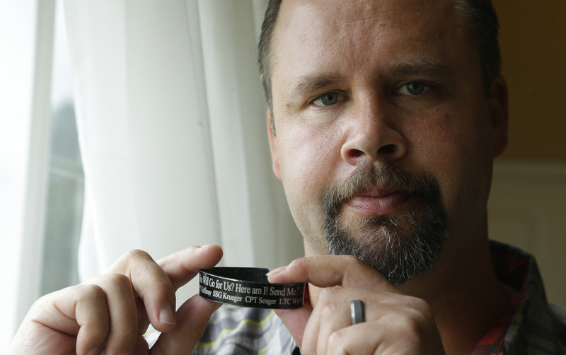 Retired Army Staff Sgt. Shawn Manning holds a memorial bracelet for members of his military unit who were killed in the 2009 mass shooting. Manning still carries two bullets in his body from the attack.