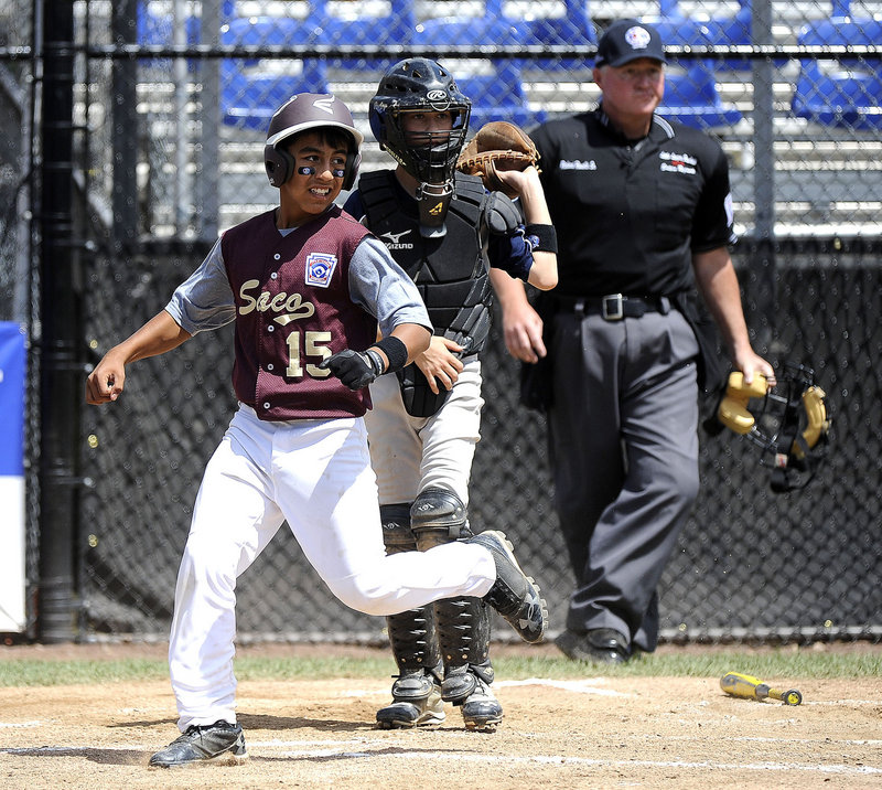 Anthony Bracamonte of Saco scores when a ball is misplayed Tuesday in the third inning of a 3-2 loss to South Burlington, Vt., at Bristol, Conn. Saco ended pool play with a 1-3 record but will advance if Massachusetts and New Hampshire lose Wednesday.