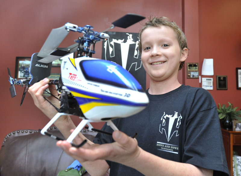 Florian Knollmann with the remote-control helicopter he helped to build at Howe & Howe Technologies in Waterboro.