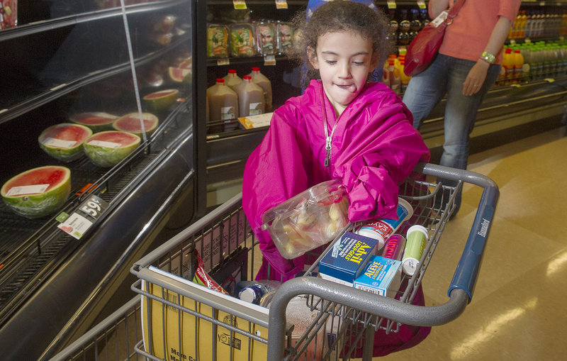 Anna Greene, 6, slips a container of fruit into a shopping cart at the Forest Avenue Hannaford in Portland, where she was shopping with her mom, Julie Greene.