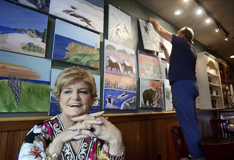 Artist Sandra Ramsey-Sterling, 76, of Haverhill, Mass., smiles while her paintings are arranged at the Lone Gull Cafe, in Gloucester, Mass., June 16. Ramsey-Sterling, who has been a beauty-pageant success, business owner and a wife and mother, has found satisfaction in recent years as a painter.