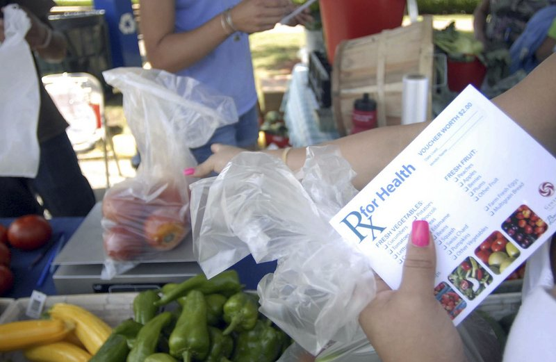 "Nely Pagan of Norwich, Conn., uses vouchers from the William W. Backus Hospital to buy vegetables at the farmers market in downtown Norwich. ""It's very helpful,"" she said. 'We have a lot of fruit and vegetables at home."""