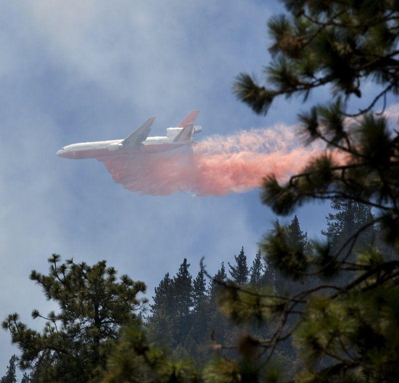 A plane drops retardant on a fire Friday in Wrightwood Calif. So far this year, fire officials have battled 4,300 wildfires in the state.