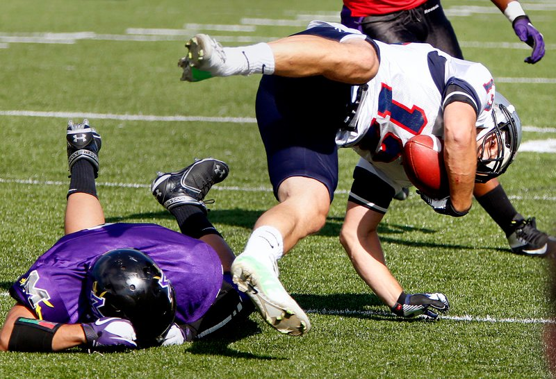 Felix Borukhov of the Metrowest Colonials is upended by Teven Colon of the Maine Sabers after making a reception Sunday during their New England Football League game. Maine remained undefeated with a 37-19 victory at Saco.
