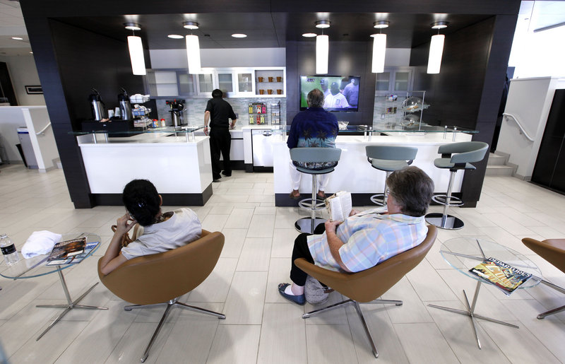Customers sit in the cafe area of Hines Park Lincoln, a dealership in Plymouth, Mich., that has been renovated to be more appealing to luxury buyers. The building is light and airy and has clusters of sumptuous leather seating.