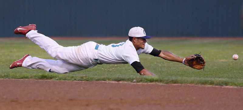 Aaron Wilson of the Old Orchard Beach Raging Tide makes a diving attempt to stop a grounder but can't prevent it from reaching the outfield Monday night. Old Orchard's season ended with a 7-3 loss in the playoffs at home.