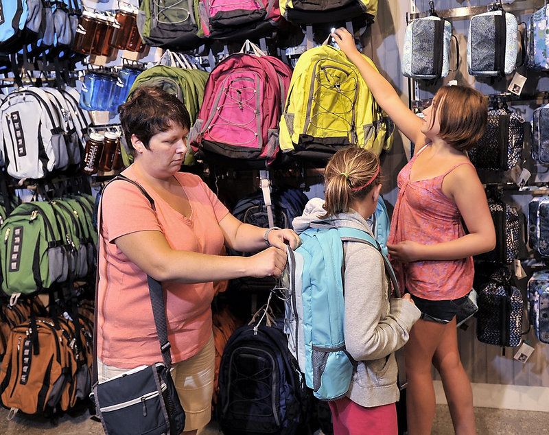 Leanne MacKay helps her daughters, Maggie, 13, and Emily, 11, choose backpacks at the L.L. Bean store in Freeport on Tuesday. The family, from Halifax, Nova Scotia, said they are combining their vacation time with back-to-school shopping for clothes and supplies.