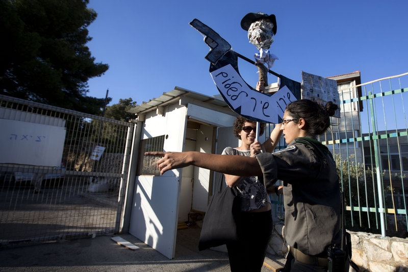 An Israeli border police officer argues with a left-wing Israeli activist protesting the resumption of housing construction in east Jerusalem on Sunday. Ahead of Israeli-Palestinian peace talks beginning Wednesday, Israel announced that it is planning for more than 3,000 new homes for Jews in the West Bank and east Jerusalem, areas the Palestinians want for a state.