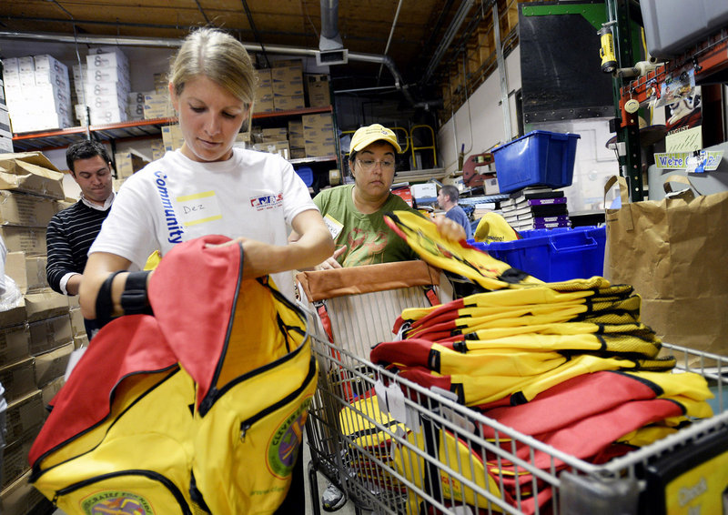 Dez Dearborn, left, and Angelea Errington-Cyr, both Unum employees, grab backpacks to hand out to other Unum employees who volunteered to stuff backpacks for students in need Wednesday, August 14, 2013. The event took place at Ruth's Reusable Resources, which spearheaded another year of helping needy schoolchildren start the school year right.