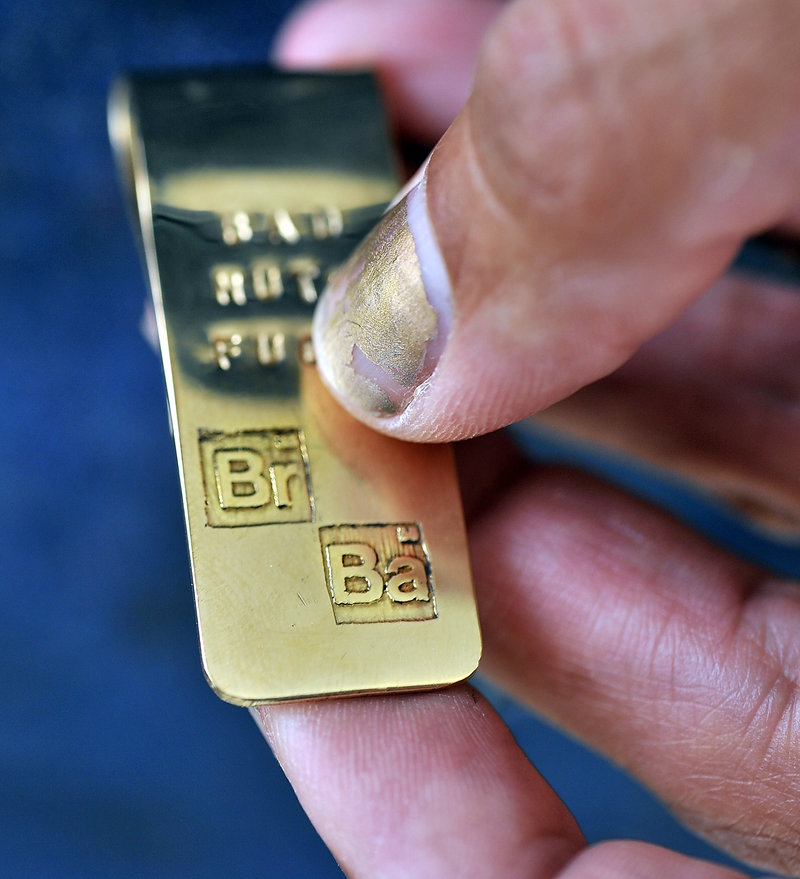 "Coco Corral of Biddeford, who created a money clip for ""Breaking Bad"" star Bryan Cranston five years ago, holds a recreation of the money clip for sale to others. Note the atomic symbols for bromine and barium, graphics the show uses for the ""Breaking Bad"" title sequence, symbolizing his character was a chemistry teacher before becoming a drug dealer."