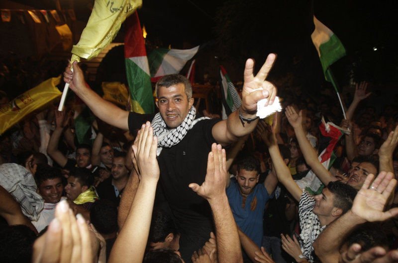 Palestinians celebrate the release of Mohammed Sawalha, center, in the West Bank Wednesday. Israel released 26 inmates, including many convicted of killings, on the eve of long-stalled Mideast peace talks, angering families of those slain.