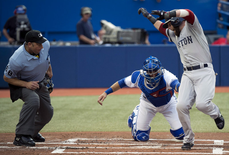 Dustin Pedroia of the Boston Red Sox tries to get around Toronto catcher J.P. Arencibia. Didn't work, Pedroia was out and the Red Sox lost 2-1 to the Blue Jays in Toronto.