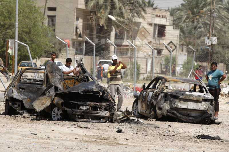 Civilians look at the aftermath of a car bomb attack in Baghdad on Thursday. More than 3,000 people have been killed in violence during the past few months, leading Iraq to ask the United States for assistance stopping the violence, which is tied to al-Qaeda.