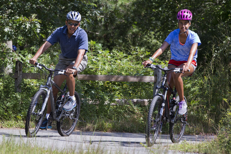 "President Obama and his daughter Malia, 15, ride bikes Friday in Manuel F. Correllus State Forest in West Tisbury, Mass. First lady Michelle Obama, with daughter Sasha, 12, passed ahead of them during their family vacation on Martha's Vineyard. The president said he's having a ""great time as always"" on the island. He returns to work Sunday."