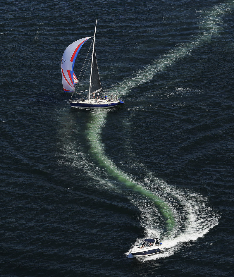 A sailboat crosses the wake of a powerboat during the regatta.