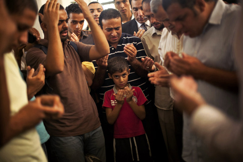 A young son of Ammar Badie prays during his father's funeral in Cairo on Sunday. The son of the Muslim Brotherhood's spiritual leader Mohammed Badie, Ammar Badie was killed by Egyptian security forces Friday in Cairo.