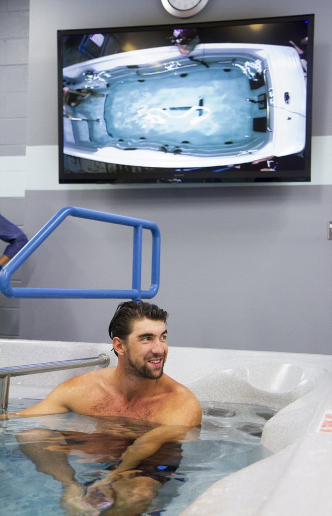 Michael Phelps talks Tuesday with local swim coaches after a demonstration of the training equipment he's helped to develop at the Michael Phelps Skill Center in Saco.