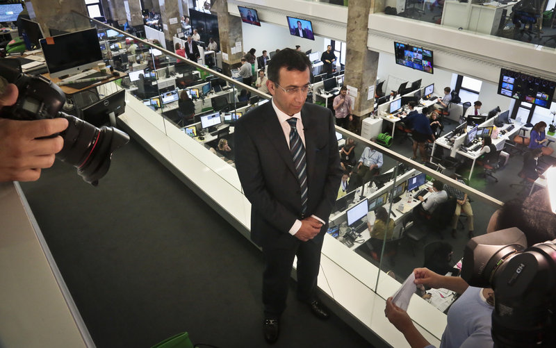 The Associated Press Ehab Al Shihabi, interim chief executive officer for Al-Jazeera America, listens during an interview overlooking the newsroom, after the network's first broadcast Tuesday in New York. It aims to air just six minutes of commercials each hour.