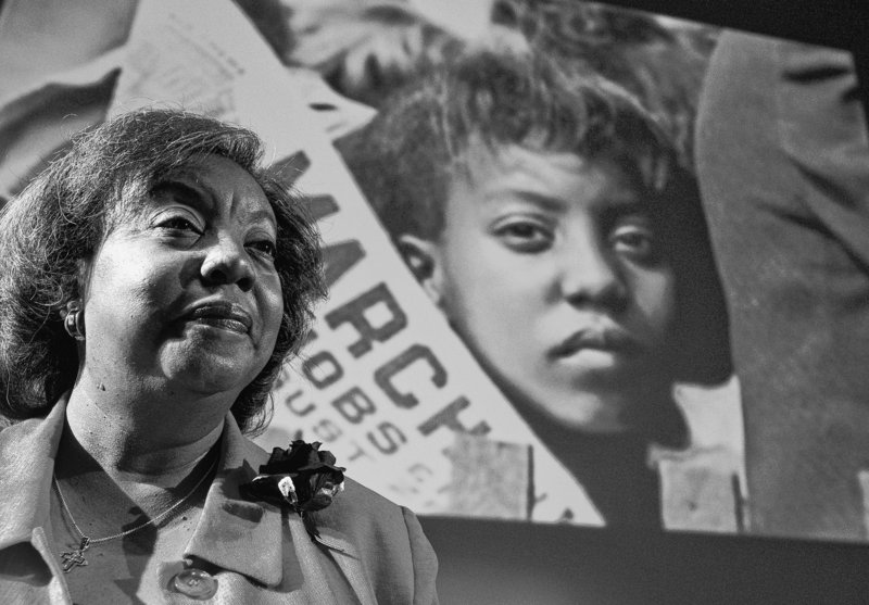 """Edith Lee-Payne, a community activist in Detroit, stands in front of an image of herself at age 12 taken at the March on Washington in 1963. """"Everyone was hanging on Dr. King's every word,"""" she says. """"When you heard him, you felt it was going to be all right."""""""
