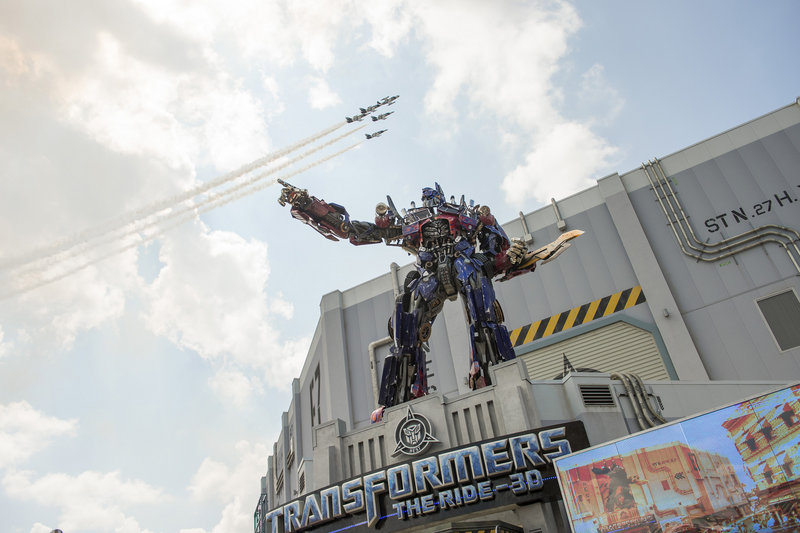 A three-story Optimus Prime figure towers at the entrance to the Transformers: The Ride-3D as a formation of private jets flies overhead at the attraction's grand opening June 20 at the Universal Orlando Resort in Orlando, Fla.