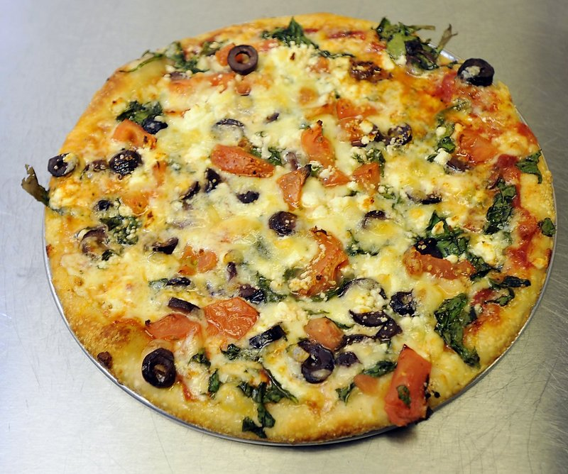 A Greek pizza with spinach, tomato, feta and Greek olives.