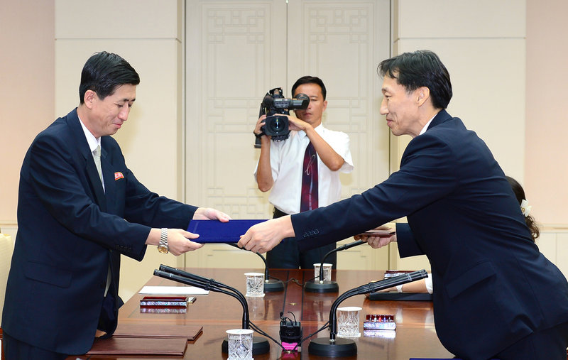 Leader of the South Korean delegation Lee Duk-haeng, right, and his North Korean counterpart Park Yong Il exchange documents Friday in Paju, South Korea.