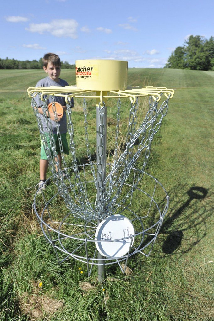Zachary Whiting, 10, of Cumberland, waits for his turn to throw after a fellow player tossed his disc into the ninth hole Friday.