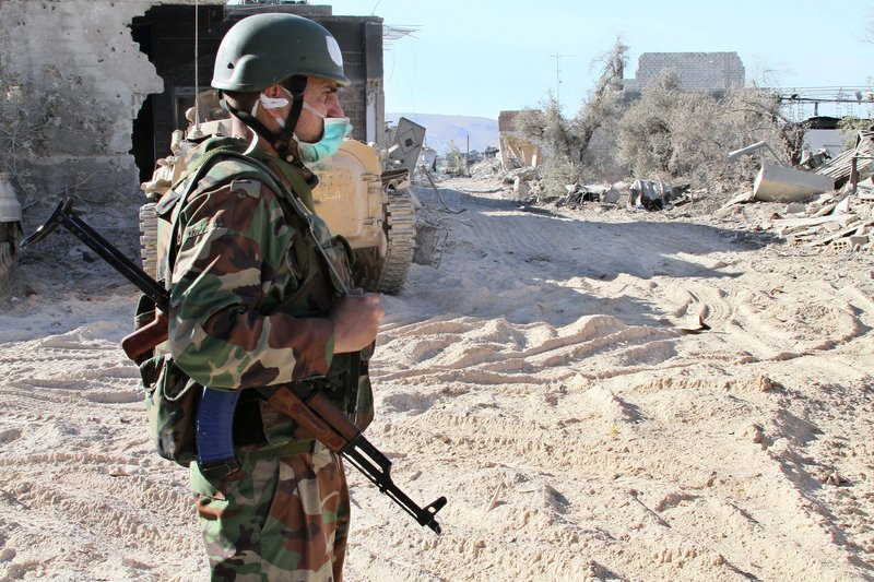 A Syrian army soldier stands guard in Damascus on Saturday. Syrian state media accused rebels of using chemical arms against government troops Wednesday.