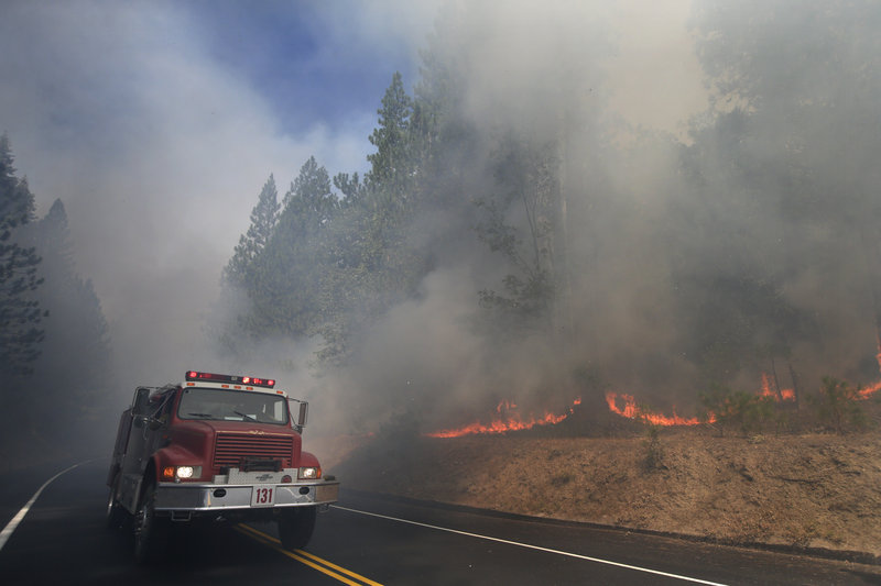 A fire truck drives past burning trees as firefighters continue to battle the Rim Fire near Yosemite National Park on Monday. The fire was 15 percent contained.