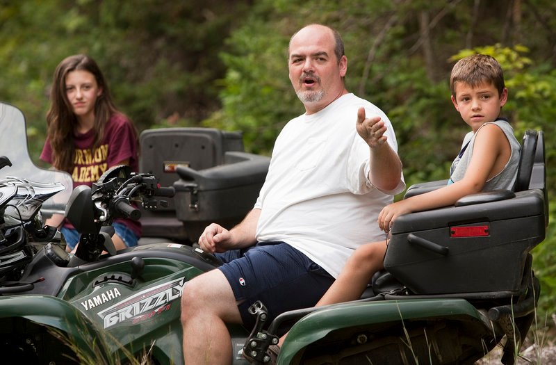 Jim Lajoie of Dayton points something out down the trail during a break while riding ATVs with his daughter Alyssa, 12, and son Ian, 8, on a trail near their home on Monday, August 26, 2013. Jim said that one of the benefits of ATV trail riding are the things you see along the way.