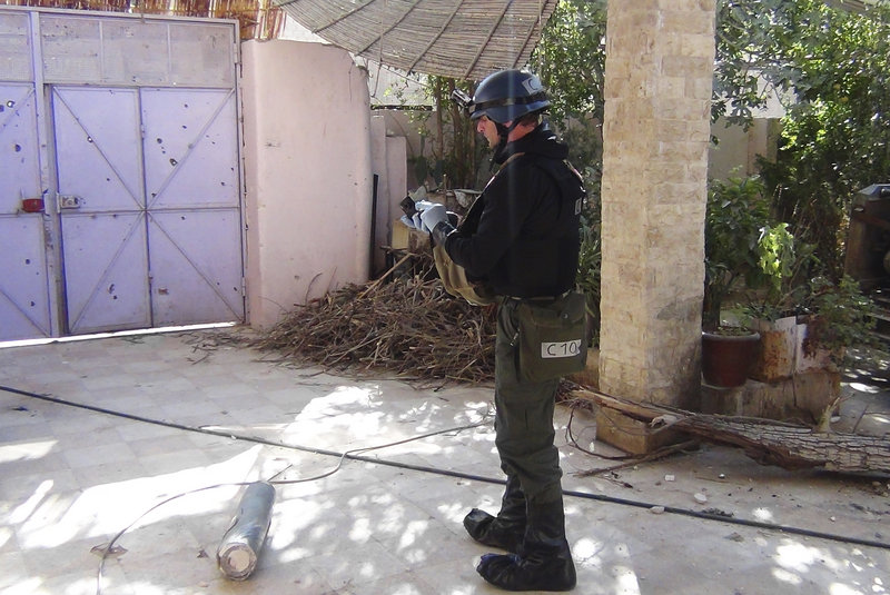 A U.N. inspector gathers evidence at one of the sites of an alleged poison gas attack in the southwestern Damascus suburb of Mouadamiya on Monday.