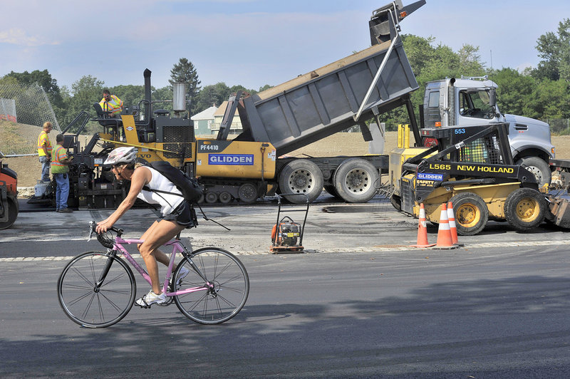 A bicyclist rides on the recently paved Baxter Boulevard as workers pave a parking area Wednesday, Aug. 28, 2013. The boulevard will reopen soon after an eight-month closure.