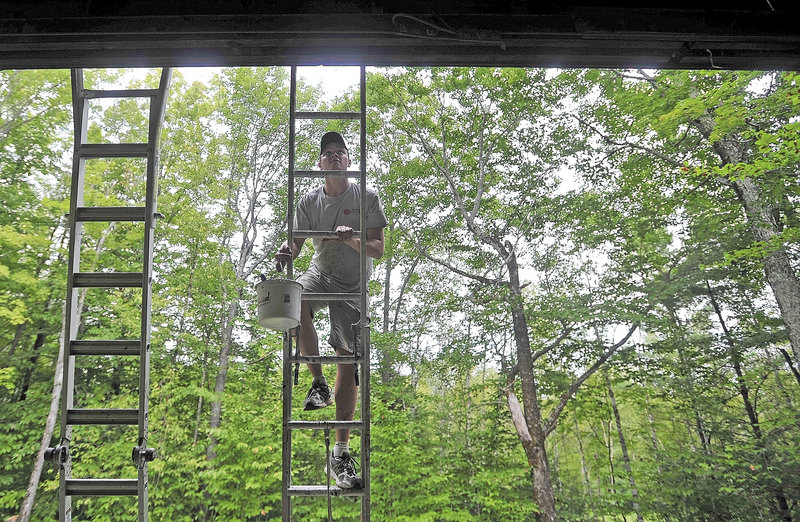 Mat Gross, of North New Portland, an employee with Backyard Farms, climbs the ladder to apply a fresh coat of paint on the Margaret Chase Smith Hall at Lake George Regional Park on the Canaan and Skowhegan town line Friday.