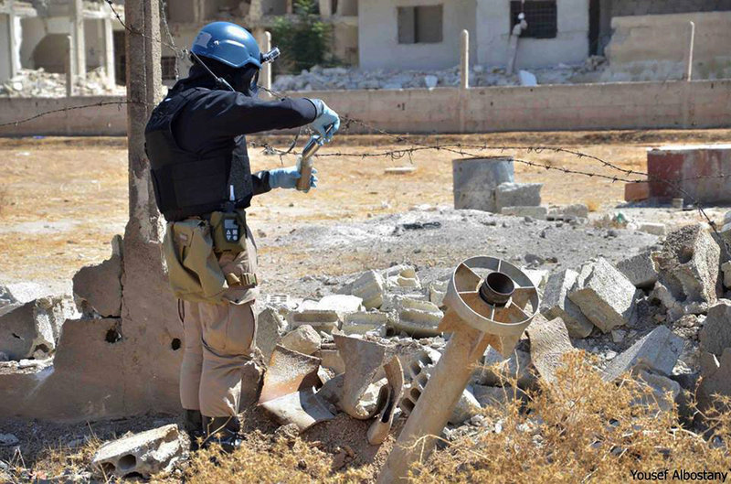 A member of a U.N. investigation team takes samples of sands near part of a missile considered likely to be one of the chemical rockets fired in the Damascus countryside of Ain Terma, Syria, on Wednesday.