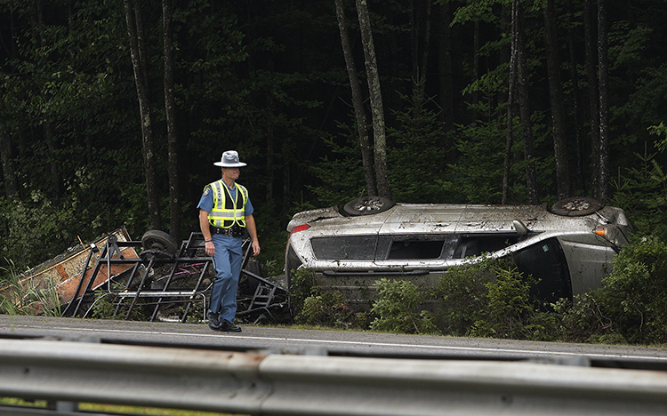 A Maine state trooper walks past a vehicle that rolled over on Interstate 295 in Freeport on Friday. One person was hospitalized.